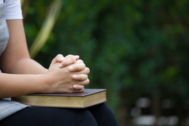Woman hands folded in prayer on a holy bible  for faith concept in nature green background Premium Photo
