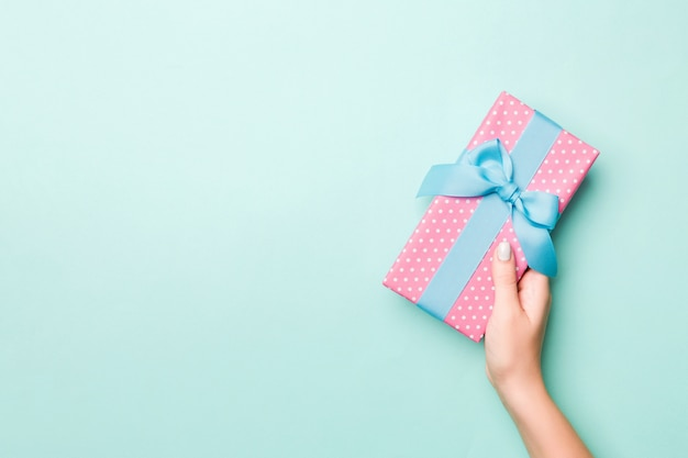 Woman hands give wrapped christmas or other holiday handmade present in colored paper. present box, decoration of gift on blue table, top view with copy space Premium Photo