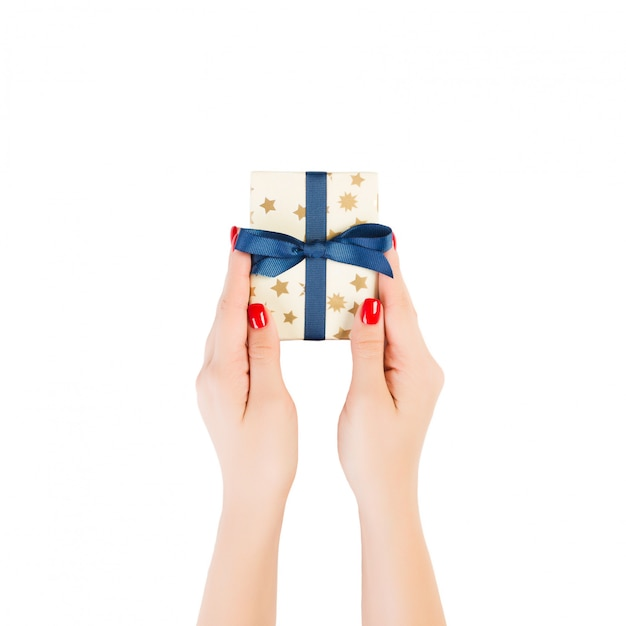 Woman hands give wrapped christmas or other holiday handmade present in gold paper with blue ribbon. isolated on white Premium Photo