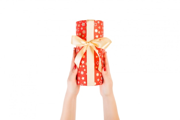 Woman hands give wrapped christmas or other holiday handmade present in red paper with gold ribbon. isolated on white Premium Photo