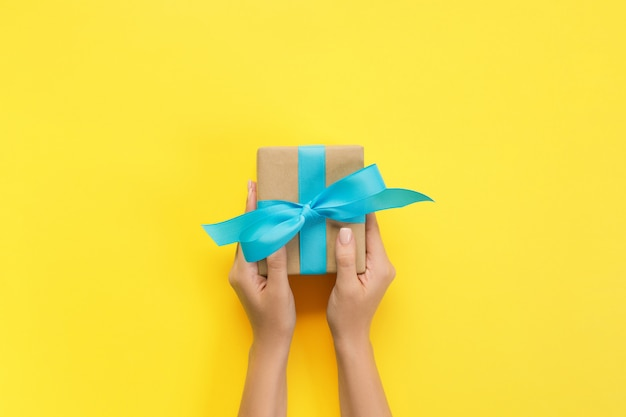 Woman hands give wrapped valentine or other holiday handmade present in paper with blue ribbon. present box, decoration of gift on yellow table, top view with copy space Premium Photo