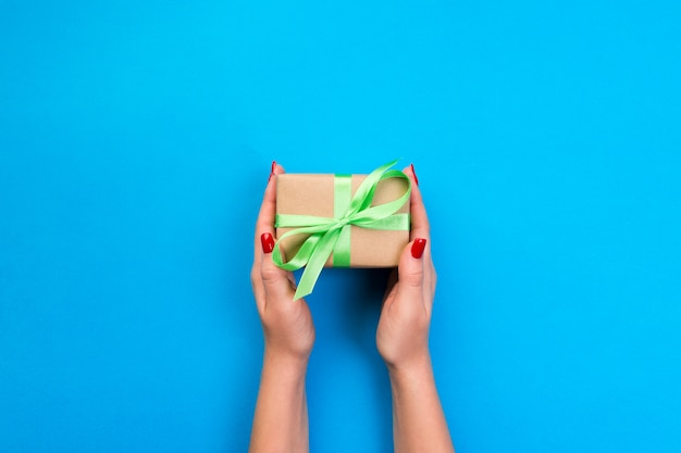 Woman hands give wrapped valentine or other holiday handmade present in paper with green ribbon. Premium Photo