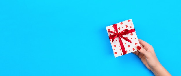 Woman hands give wrapped valentine or other holiday handmade present in paper with red ribbon. Premium Photo