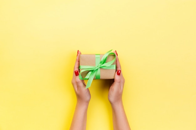 Woman hands give wrapped valentine in paper with red ribbon. Premium Photo