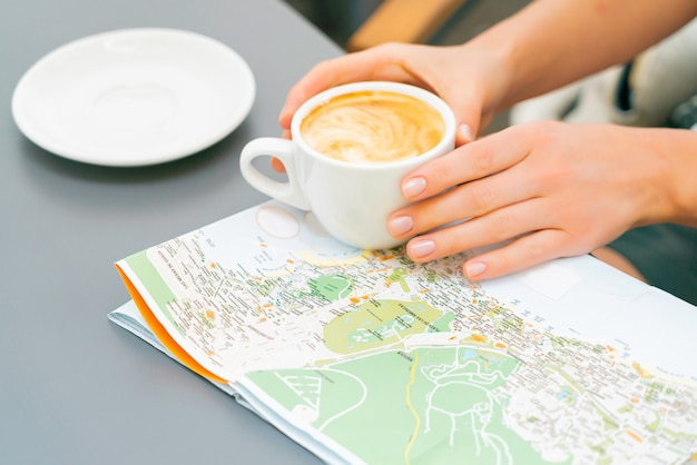 Woman hands hold coffee cup over the map on the table. girl travel canary islands and looking for a new place to visit. sunny day in a street cafe. Free Photo