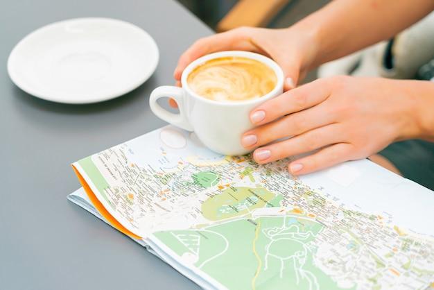 女性の手はテーブルの上の地図の上にコーヒーカップを保持します。女の子旅行カナリア諸島と訪問する新しい場所を探しています。ストリートカフェで晴れた日。 無料写真