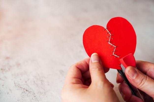 女性の手はホッチキスで修正赤失恋を保持します。 Premium写真