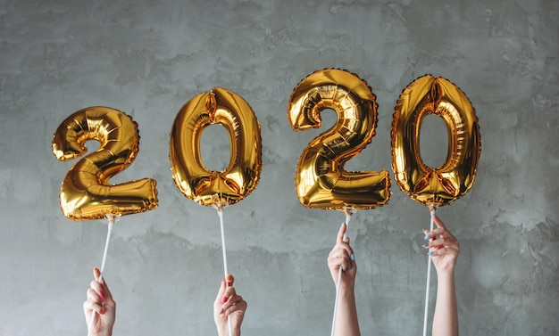 The woman hands holding 2020 numbers balloons on grey concrete wall background Premium Photo