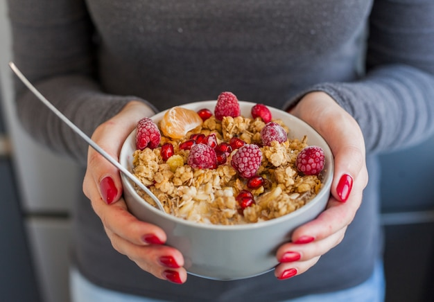Woman hands holding cereal and fruit bowl Free Photo