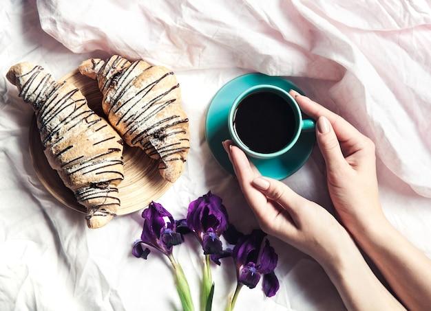 ベッドで一杯のコーヒーを保持している女性の手。美しい花とブレスレット付きの時計 Premium写真