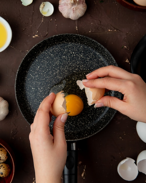 Woman hands holding eggshell with egg yolk in frying pan on maroon table Free Photo