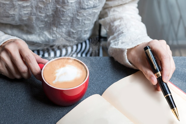 Woman of hands holding hot cup of coffee latte and writing pen on book. Premium Photo