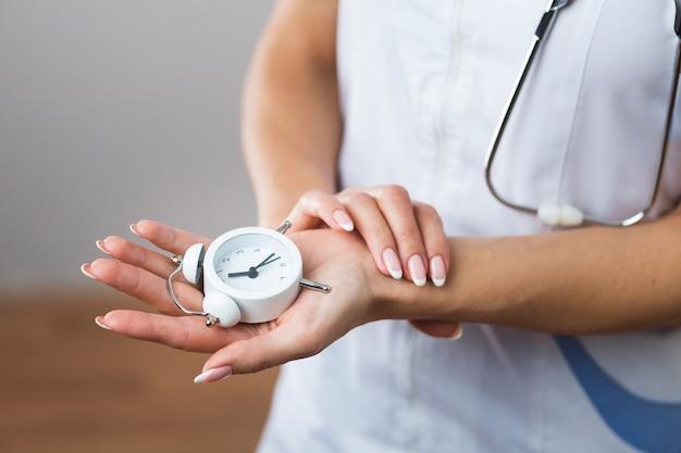 Mani della donna che tengono un piccolo orologio Foto Gratuite
