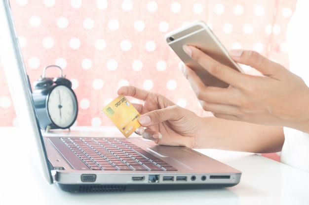 Woman hands holding mobile phone and plastic credit card. e-payment. online shopping Premium Photo