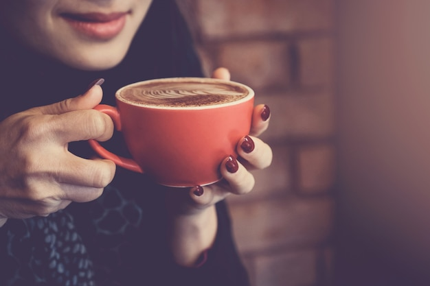 Woman hands holding red cup of coffee latte Premium Photo