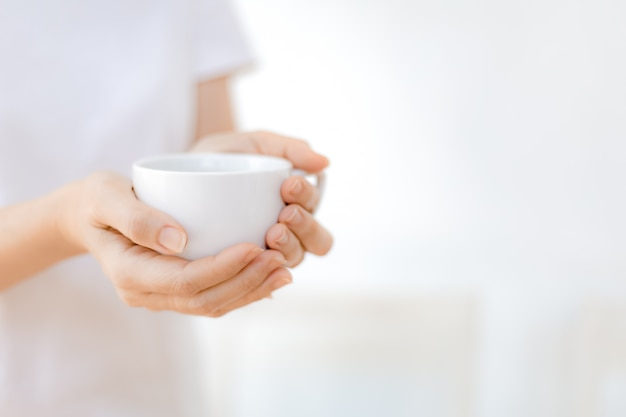 Woman hands holding white coffee cup Premium Photo