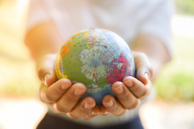 Woman hands holding world ball on her hand with natural green background. world environment day concept. Premium Photo