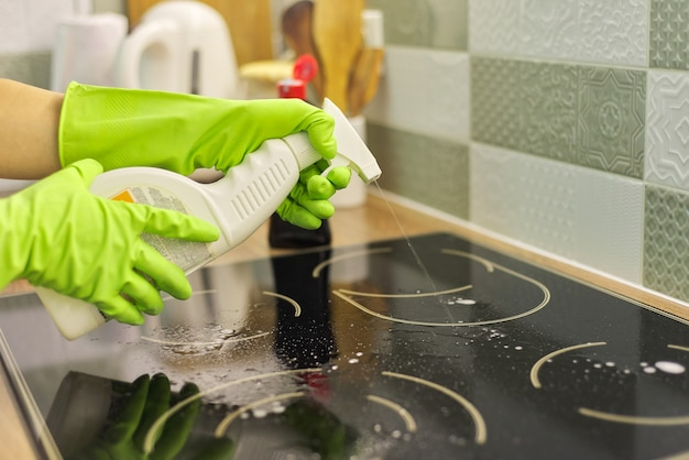 女性が手袋をはめて、スポンジと洗剤でキッチンの電気セラミックコンロを掃除します Premium写真