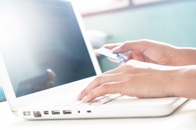 Woman hands on keyboard of laptop and holding credit card, online shopping concept with copy space Free Photo