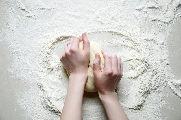 Woman hands kneads the dough with flour on the white kitchen table. top view flat lay. Premium Photo