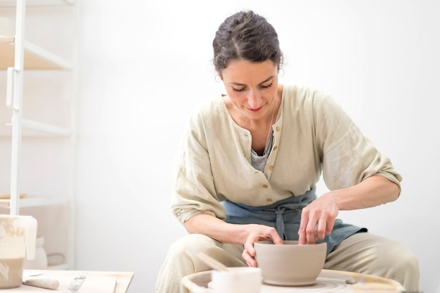 Woman hands makes clay pot on the pottery wheel Premium Photo