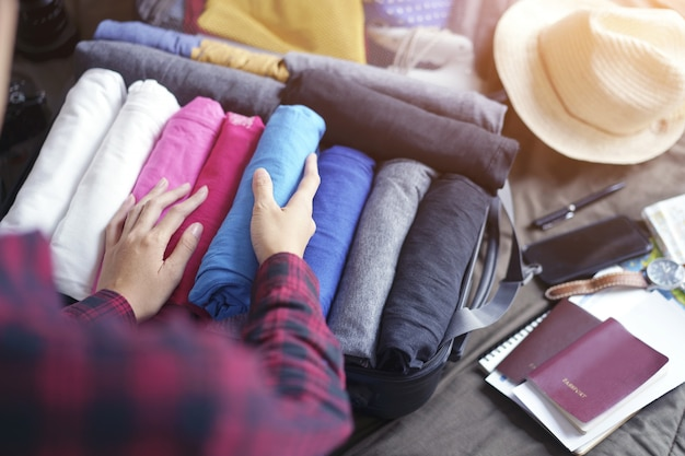 Woman hands pack clothes in suitcase bag on bed, prepare for new journey and travel to long weekend. Premium Photo