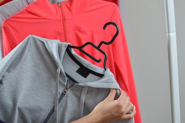 Женщина руки выбирая спортивную куртку в магазине Premium Фотографии