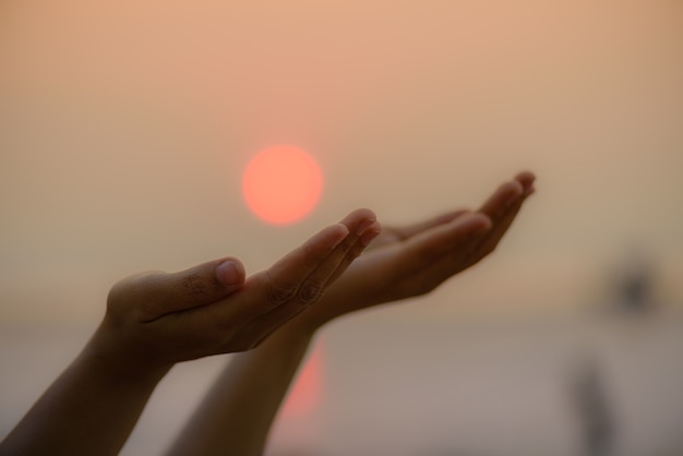 Woman hands praying for blessing from god during sunset background. hope concept. Premium Photo