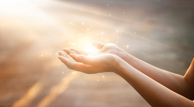 Woman hands praying for blessing from god on sunset background Premium Photo