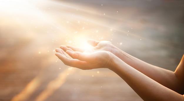 일몰 배경에 신의 축복을 위해기도하는 여자 손 프리미엄 사진