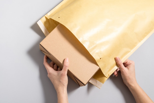 大きな郵便封筒の中に段ボール箱を置く女性の手 Premium写真