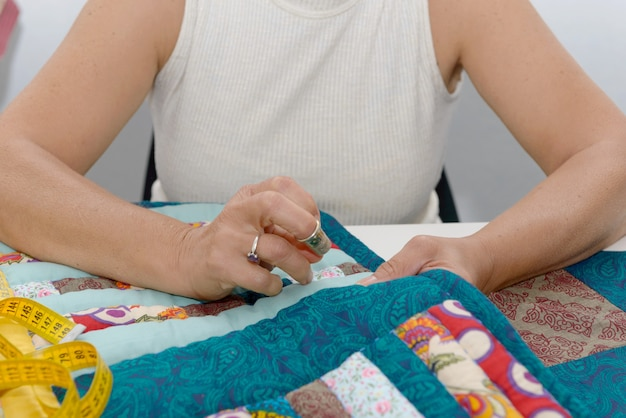 Woman hands sewing for finish a quilt. Premium Photo