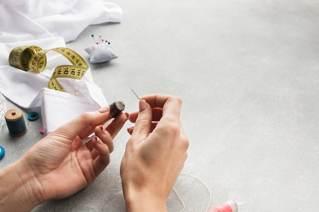 Woman hands sewing a white shirt high view Free Photo