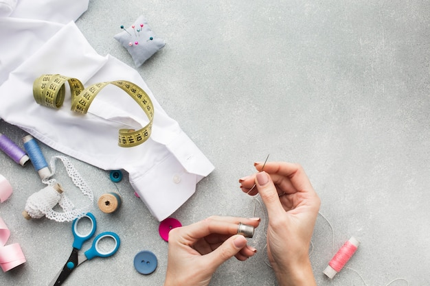 Woman hands sewing a white shirt with copy space Free Photo