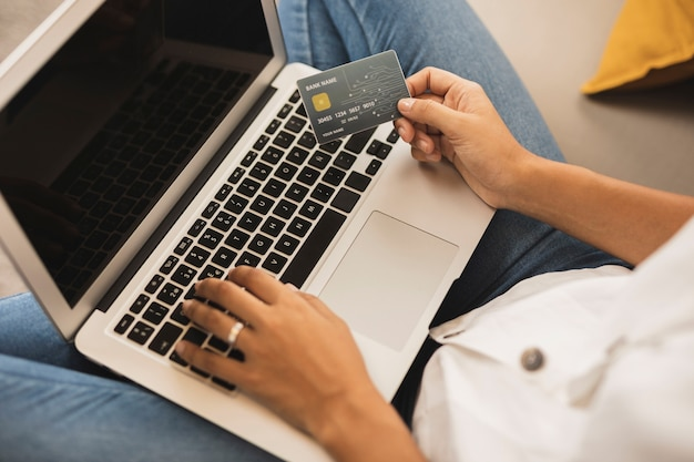 Woman hands typing and holding a credit card Free Photo