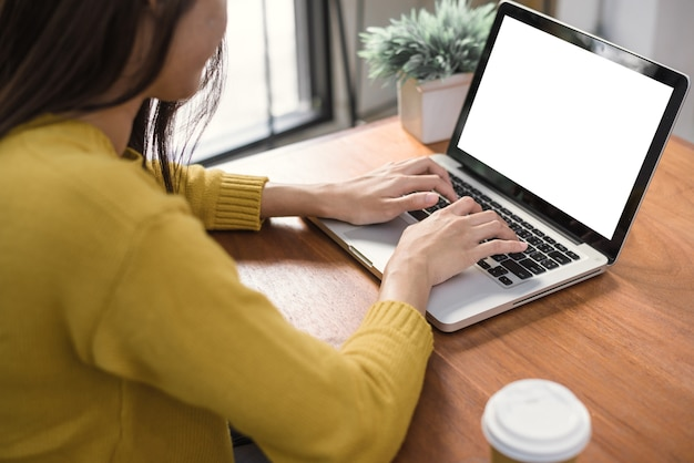 Woman hands typing laptop computer with blank screen for mock up template background | Premium Photo