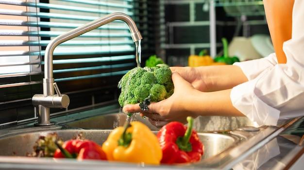 Женщина руки мыть овощи для приготовления веганский салат Premium Фотографии