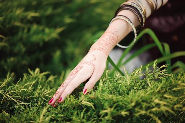 Женщина руки с черным менди тату. руки индийской невесты женщина с черными татуировками хной. мода. индия Premium Фотографии