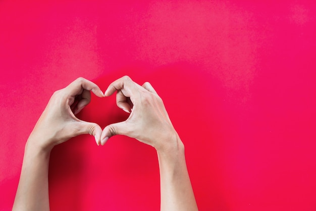 Woman hands with heart shape on red background with copy space Premium Photo