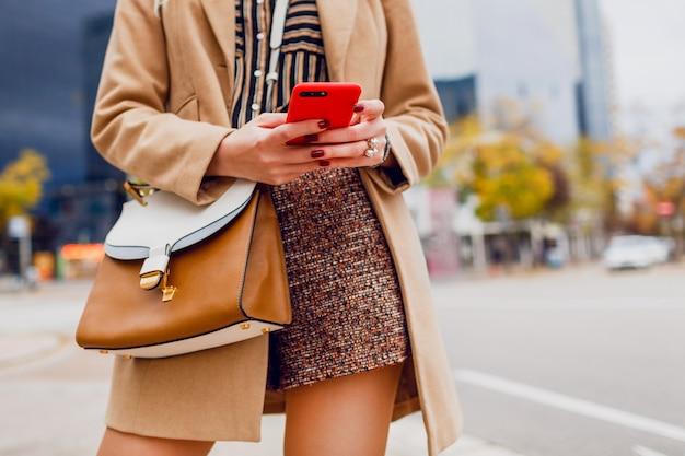 휴대 전화로 여자 손입니다. 베이지 색 코트 채팅에 세련 된 소녀입니다. 현대 도시. 무료 사진