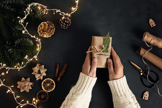 재활용 된 공예 종이로 친환경 대체 녹색 크리스마스 선물 포장 여자 손 프리미엄 사진