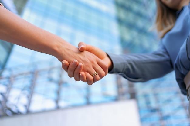 Handshaking della donna all'aperto sopra la costruzione moderna di affari di vetro, immagine del primo piano Foto Gratuite