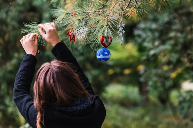 Woman hanging christmas toys on twig in forest Free Photo