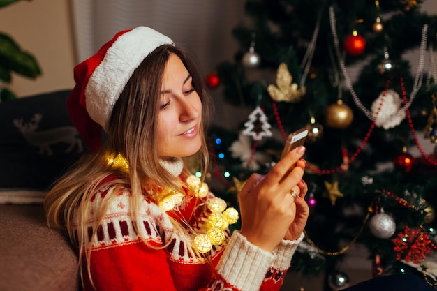 Woman hanging in internet for christmas using smartphone. girl celebrating new year alone at home. social network Premium Photo
