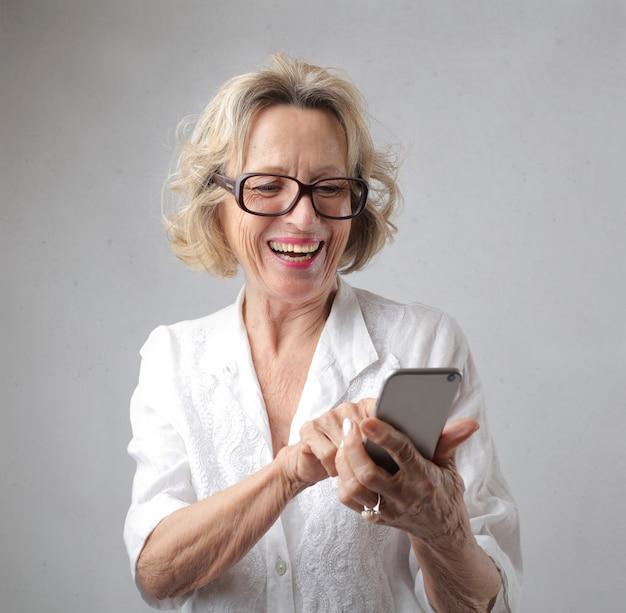 Donna che naviga felicemente in internet e comunica con amici e familiari tramite smartphone Foto Gratuite