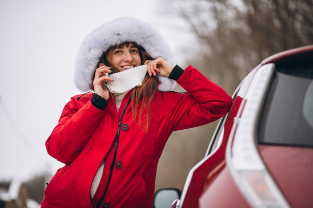 Woman happy talking on the phone outside by car in winter Free Photo