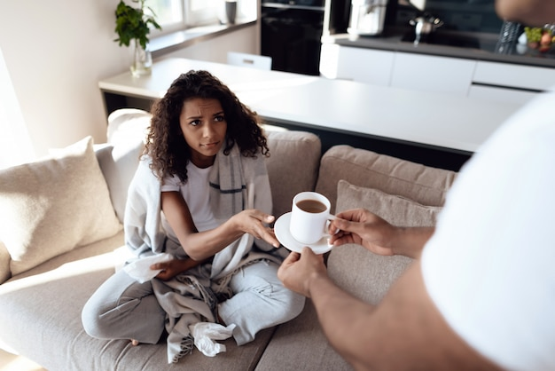The woman has a cold and the man brought her hot tea. Premium Photo