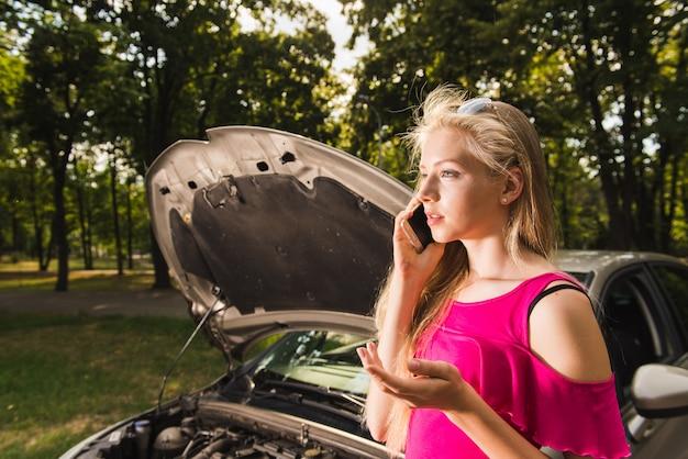女性は壊れた車についての会話をしています Premium写真