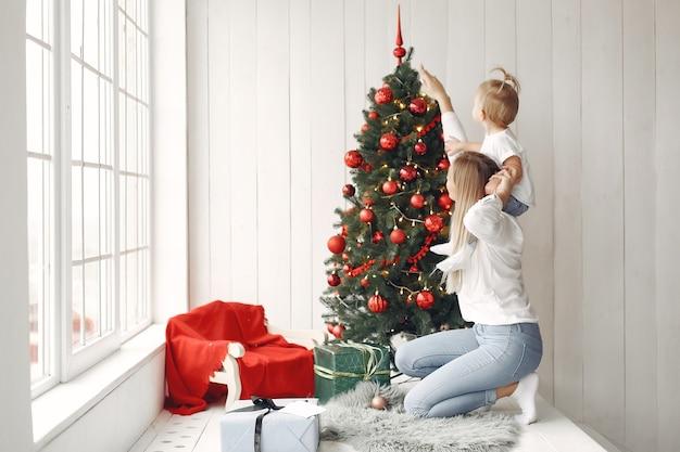 女性はクリスマスの準備を楽しんでいます。白いシャツを着たお母さんが娘と遊んでいます。家族はお祭りの部屋で休んでいます。 無料写真