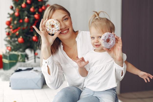 여자는 크리스마스를 준비하는 재미 있습니다. 흰색 셔츠에 어머니는 그녀의 딸과 함께 재생됩니다. 가족은 축제 방에서 쉬고 있습니다. 무료 사진